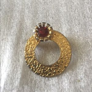 Pin goldstone with red stone